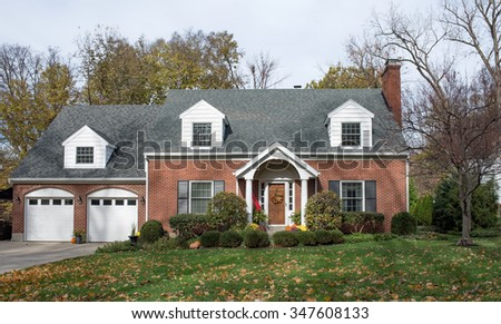 Stately Cape Cod House in Fall - stock photo
