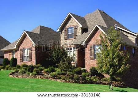 Stately nicely landscaped upscale brick home somewhere in the midwest USA. - stock photo