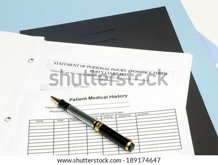 Statement of personal injury form with patient chart and pen. - stock photo