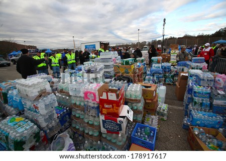 STATEN ISLAND, NEW YORK CITY - NOVEMBER 4 2012:Volunteers & national guard assembled at New Dorp High School to render aid to people recovering from Hurricane Sandy.Stacks of water ready to distribute - stock photo