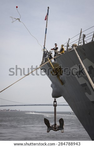 STATEN ISLAND, NY - MAY 20 2015: Linesmen work on the bow of USS Barry (DDG 52) guided-missile destroyer mooring for Fleet Week NY at Sullivans Pier with the Verrazano-Narrows Bridge in background.  - stock photo