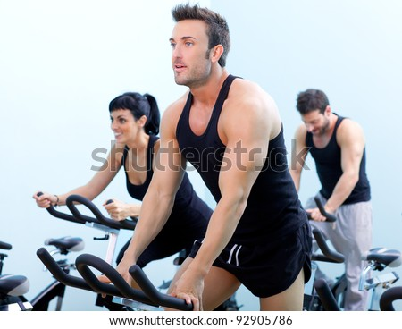 Stationary bicycles fitness man in a gym sport club - stock photo