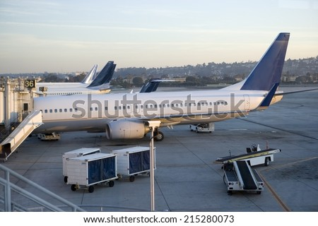 Stationary commercial aircraft at airport boarding gate, side view, elevated view - stock photo