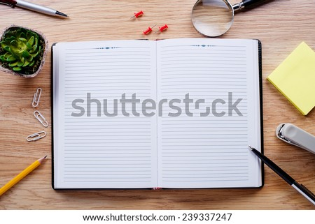Stationery, flower pot, and the open notebook in the midst of a wooden table - stock photo