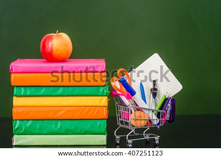 Stationery near empty green chalkboard. Space for text - stock photo