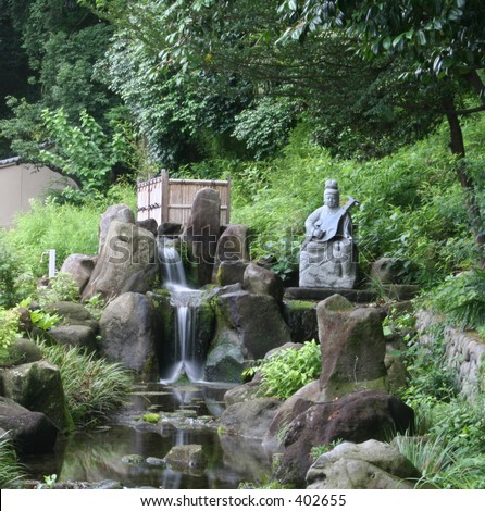 Statue and water fall at a Buddhist Temple outside of Tokyo, Japan. - stock photo