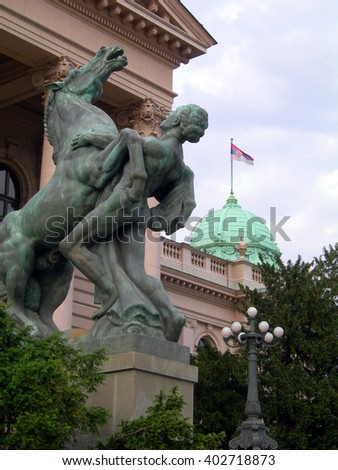 statue monument of man and horse entry to House of the National Assembly of Serbia Parliament building with national flag Belgrade  Europe - stock photo