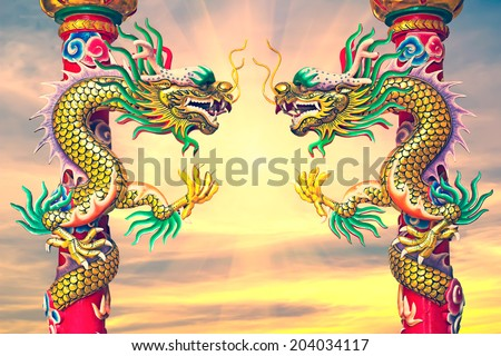 Statue of a dragon wrapped around a pole. - stock photo