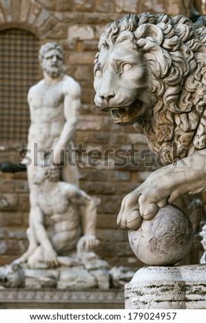 Statue of a lion at the Loggia dei Lanzi in Piazza della Signoria in Florence (Tuscany, Italy). Hercules and Cacus (Baccio Bandinelli) statue in front of the Palazzo Vecchio background. - stock photo