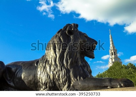 Statue of a lion near the Nelson column at Trafalgar Square in London. UK - stock photo