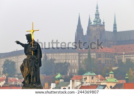 Statue of a priest with golden cross decorates the Charles bridge with the Prague castle in the background, Prague, Czech Republic - stock photo