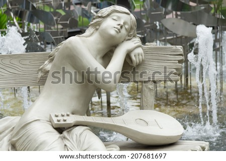 Statue of a woman sleeping on chairs along the way. - stock photo