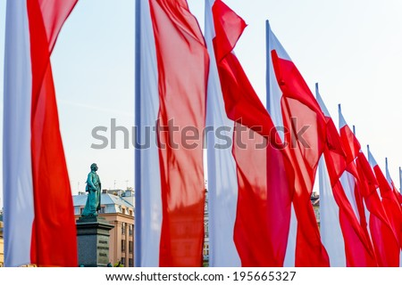 Statue of Adam Mickiewicz on the Main square in Krakow surrounde by polish national flags - stock photo