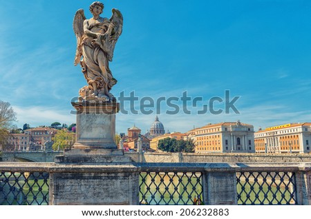 Statue of angel on Rome bridge with San Pietro dome on background - stock photo
