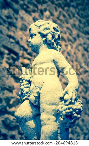 Statue of Bacchus (Dionysus) with grapes in his hands against rough stone wall. Garden sculpture. (Chateauneuf du Pape, Provence, France) Aged photo.  - stock photo
