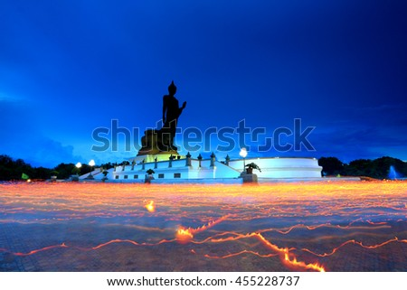 Statue of big Buddha with candlelit of buddhist people walking around in the evening. - stock photo