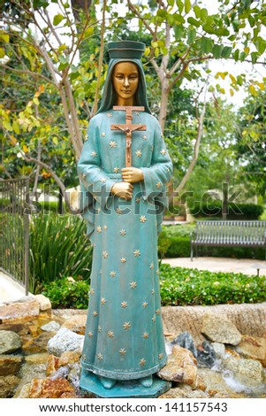 Statue of Blessed Virgin stands in a garden of the San Fernando Mission - stock photo