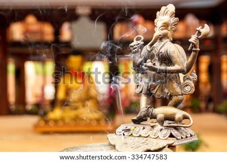 Statue of Buddha behind Ganesha with incense stick - stock photo