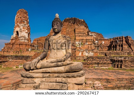 Statue of giant seated Buddha in ruins at Ayuthaya, Thailand - stock photo