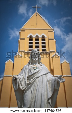 Statue of Jesus Christ and Church. Statue of Jesus Christ in front of St. Willibrordus church in Curacao, Netherlands Antilles. Sint Willibrordus Roman Catholic church was built between 1884 and 1888. - stock photo