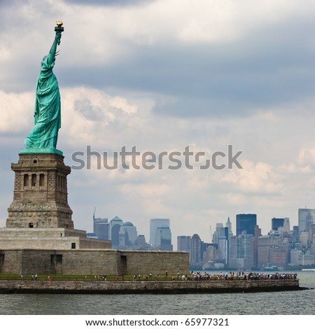 Statue of Liberty in New York City with Skyline and cloudy sky - stock photo