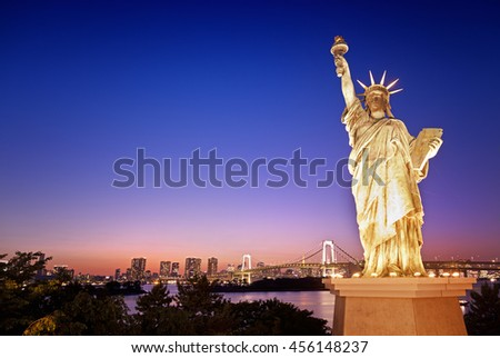 Statue of Liberty in Odaiba, Tokyo during sunset / twilight with Rainbow bridge and Tokyo city in Background - stock photo