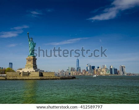 Statue of Liberty on a sunny day, Manhatten in the background. This is a photo-montage, because the statue faces to the viewer! - stock photo