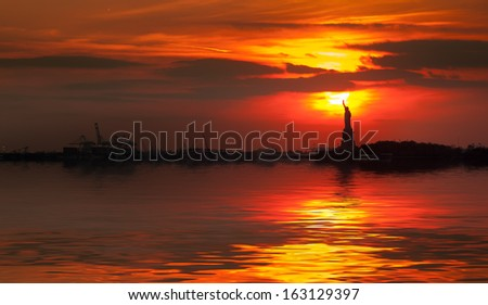 Statue of Liberty silhouette and the setting sun with water reflection - stock photo
