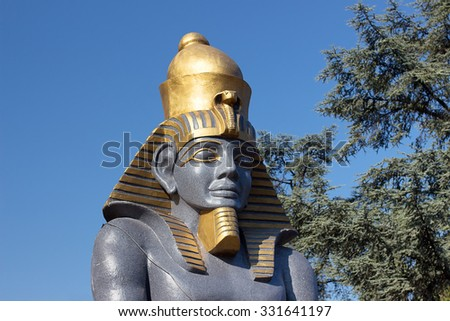 Statue of Pharaoh against a background of blue sky and trees. Decorative sculptures with Egyptian motives.  - stock photo