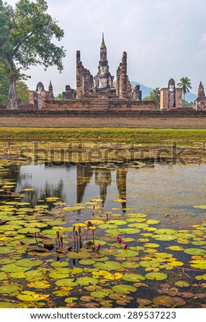 Statue of seated Buddha in meditation reflected across a lotus pond in Wat Mahathat temple in Sukhothai, Thailand. - stock photo
