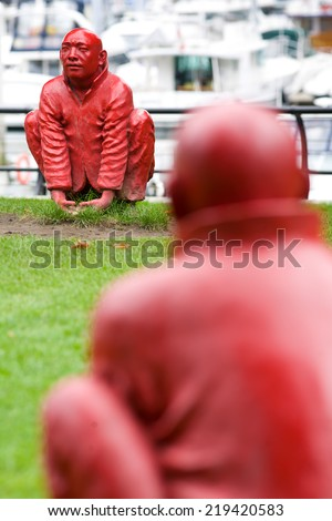 statue of squatting buddhist monks, public sculpture titled 'Meeting' by Wang Shugang, Cardero Park, Vancouver, British Columbia - stock photo