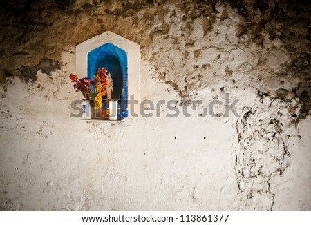 Statue of the virgin Mary with flowers - stock photo