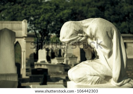 Statue of weeping woman on a grave - stock photo