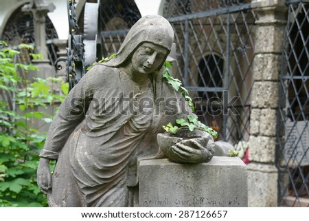 Statue of woman with tendrils of ivy, leaning on a tombstone, St. Peter's Cemetery, Salzburg. - stock photo