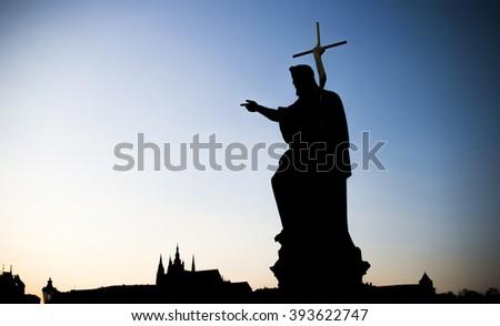 Statue on Charles Bridge (Karluv most, 1357), a famous bridge that crosses Vltava River in Prague, Czech Republic, high contrast concept, sunset - stock photo