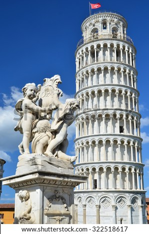 Statue with 3 cherubs in front of the leaning tower of Pisa at Pisa, Italy - stock photo