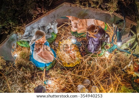 Statues in a Christmas Nativity scene, the Blessed Virgin Mary and Saint Joseph watch over the Holy Child Jesus in a manger in the straw as the ox and the donkey are warming - stock photo