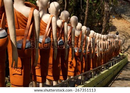 Statues of Buddhist nuns line the stairway at  Sambuk Mountain Monastery,  Kratie, Cambodia - stock photo