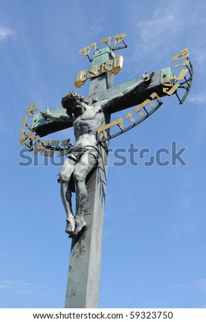Statues on Charles Bridge in Prague depicting Jesus with Hebrew inscription. - stock photo