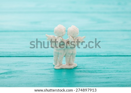 Statuette of angels on blue wooden background. Selective focus - stock photo