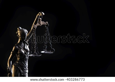 Statuette of the goddess of justice Themis with scales - isolated on black background. Law concept - stock photo