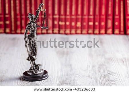 Statuette of Themis the symbol of law on old wooden floor with legal codes. Law concept - stock photo