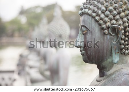 Statute of Buddha in a row. Close-up on the face of Buddha. - stock photo