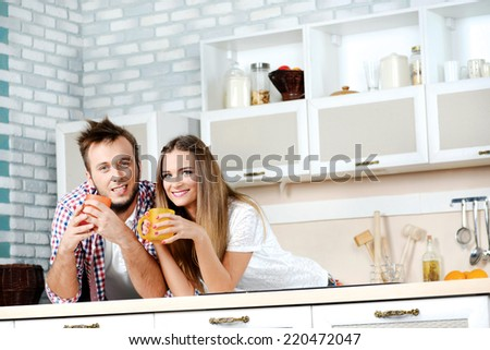 Staying at home. Young couple in love drinking hot tea while standing and cooking in the kitchen and holding a cup looking and smiling at the camera - stock photo