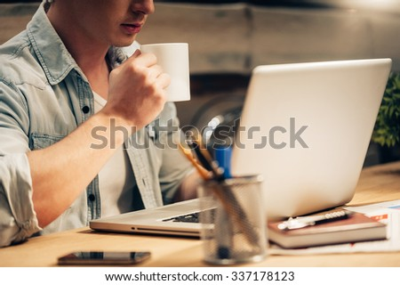 Staying concentrated. Close-up of confident young man working late and drinking coffee while sitting at his working place  - stock photo