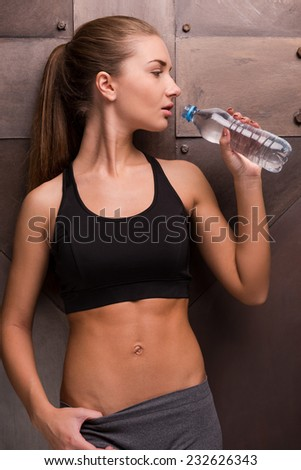 Staying hydrated. Beautiful young woman drinking water from bottle while standing against metal background - stock photo