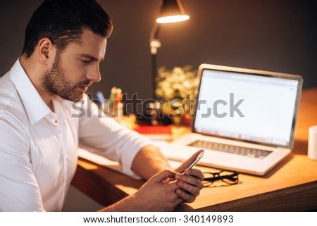 Staying in touch even late hours. Confident young man looking at his smart phone while sitting at his working place at night time - stock photo