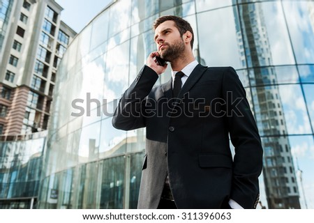 Staying in touch with clients. Low angle view of confident young businessman talking on the mobile phone and looking away while standing outdoors with office building in the background - stock photo