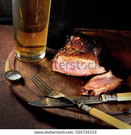 Steak  and beer on a wooden background - stock photo