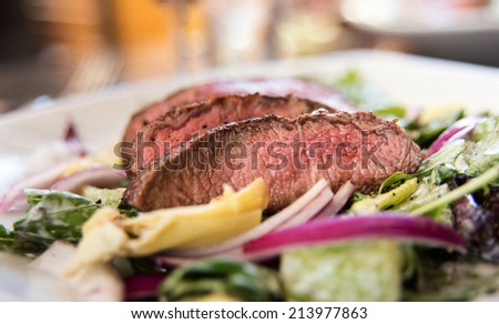 Steak and Greens Salad with Grass Fed Beef and Red Onions - stock photo
